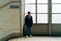 Uomo adulto in piedi alla finestra vicino alle scale in ingresso — Foto stock
