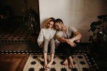 Романтичный мужчина и женщина, сидящие на полу дома вместе — стоковое фото