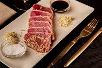 Raw sliced tuna steak on platter with sauce on black background — Stock Photo