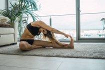 Fiduciosa donna tatuata in lingerie nera seduta su tappeto contro la finestra e praticare yoga asana — Foto stock