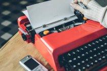 Téléphone portable et machine à écrire rouge vif avec stylo main humaine — Photo de stock