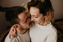 Happy man and woman sitting and embracing at home together — Stock Photo