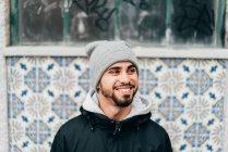 Retrato de alegre animado turista masculino em pé na parede com azulejos azuis — Fotografia de Stock