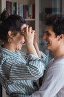 Lachendes junges Paar im Pyjama umarmt sich zu Hause — Stockfoto