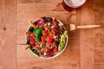 Чаша вкусного овощного салата с авокадо на деревянном столе — стоковое фото