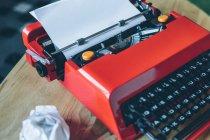Gros plan machine à écrire rouge sur petite table avec feuille de papier insérée — Photo de stock