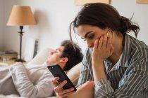Junge traurige Frau sitzt und nutzt Smartphone, während ihr Freund im Bett schläft — Stockfoto
