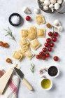 Raviolis et épices non cuits avec tomates et champignons sur la table — Photo de stock