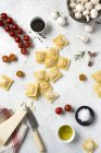 Ravioles y especias sin cocer con tomates y champiñones sobre la mesa - foto de stock
