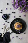 Stapel von appetitlichen leckeren Crumpets mit Heidelbeeren und lila Blumen auf schwarzem Teller auf grauem Hintergrund — Stockfoto