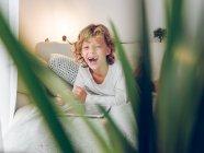 Laughing boy avec tablette sur canapé à la maison — Photo de stock