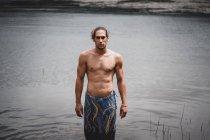 Uomo senza maglietta in piedi in acqua di fiume, guardando in macchina fotografica — Foto stock