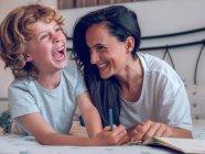 Женщина и симпатичный ребенок лежат на удобной кровати и вместе раскрашивают картинки в блокноте — стоковое фото