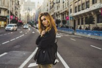 Young blonde woman posing on road in city — Stock Photo