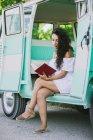 Молода жінка в Літнє плаття сидять і читання у Ван — стокове фото