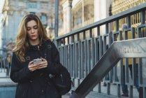 Жінка за допомогою смартфона поблизу під землею в місті — стокове фото