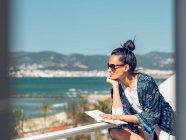 Mujer con libro en balcón - foto de stock