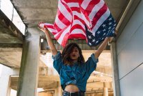 Young woman in denim clothes holding flag of America — Stock Photo