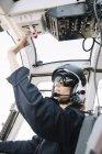 Concentrati pilota femminile nel casco che si siede e operano in elicottero — Foto stock
