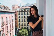 Молодая женщина стоит на балконе с фотокамерой в старом городе — стоковое фото