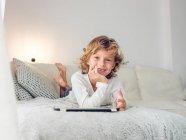 Adorable garçon avec les cheveux bouclés regardant la caméra tout en étant couché sur un canapé confortable près des oreillers avec tablette numérique — Photo de stock