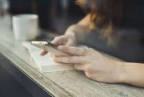 Close-up of woman using smartphone in cafe behind window pane — Stock Photo