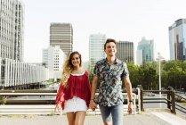 Пара, держащаяся за руки и идущая по улице — стоковое фото