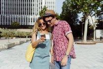 Couple naviguant smartphone dans la rue — Photo de stock