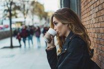 Mujer joven con la taza de papel de la situación del café en la calle - foto de stock