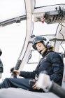 Focalizzato femmina seduta pilota e operano in elicottero — Foto stock