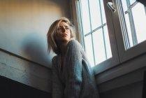 Chère jeune femme blonde en pull assis à la fenêtre et regardant loin — Photo de stock