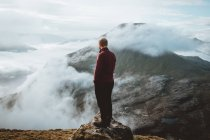 Unrecognizable hiker standing on mountain edge in clouds on Feroe Islands — Stock Photo