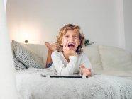 Garçon gai utilisant avec tablette numérique couché sur le canapé — Photo de stock