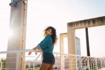 Mujer sensual joven en ropa de mezclilla de pie en el balcón cerca de barandilla en la luz del sol - foto de stock