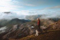 Escursionista in piedi sul bordo della montagna e guardando la vista sulle isole Feroe — Foto stock