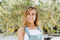 Lächelnde Frau am Baum — Stockfoto