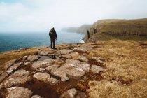 Randonneur méconnaissable homme debout sur la côte avec bâton et regardant l'océan sur les îles Feroe — Photo de stock