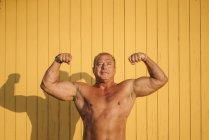 Muscular mayor hombre poses amarillo fondo - foto de stock