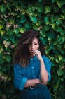 Junge sinnliche afrikanisch-amerikanische Frau in Jeanskleidung steht vor grünem Laub und blickt in die Kamera — Stockfoto