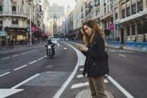 Femme utilisant un smartphone sur la route en ville — Photo de stock