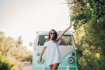 Cheerful brunette woman posing in front of retro van in nature — Stock Photo