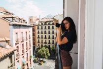 Молодая женщина стоит на балконе в старом городе с фотоаппаратом — стоковое фото