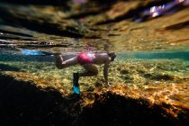 Unrecognizable boy diving in sea over rock — Stock Photo