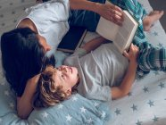 З верхнього кадру милого хлопчика лежить на гарному ліжку і читає цікаву книжку з допомогою матері. — стокове фото