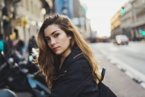 Young woman leaning standing in city and looking at camera — Stock Photo