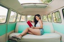Frau sitzt in Retro-Wohnwagen und liest Buch — Stockfoto