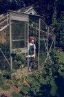 Ragazzo in piedi nel carattere della serra e guardando altrove — Foto stock