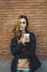 Portrait of young woman with paper cup of coffee standing against brick wall — Stock Photo
