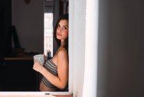 Молодая женщина с чашкой кофе, опираясь на стену возле окна — стоковое фото