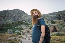 Hombre joven en sombrero con mochila de pie en el fondo de la montaña - foto de stock